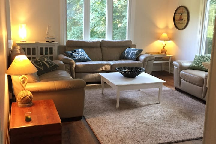 Living room on main floor with electric fireplace and large screen smart TV with cable, Netflix and Prime Video