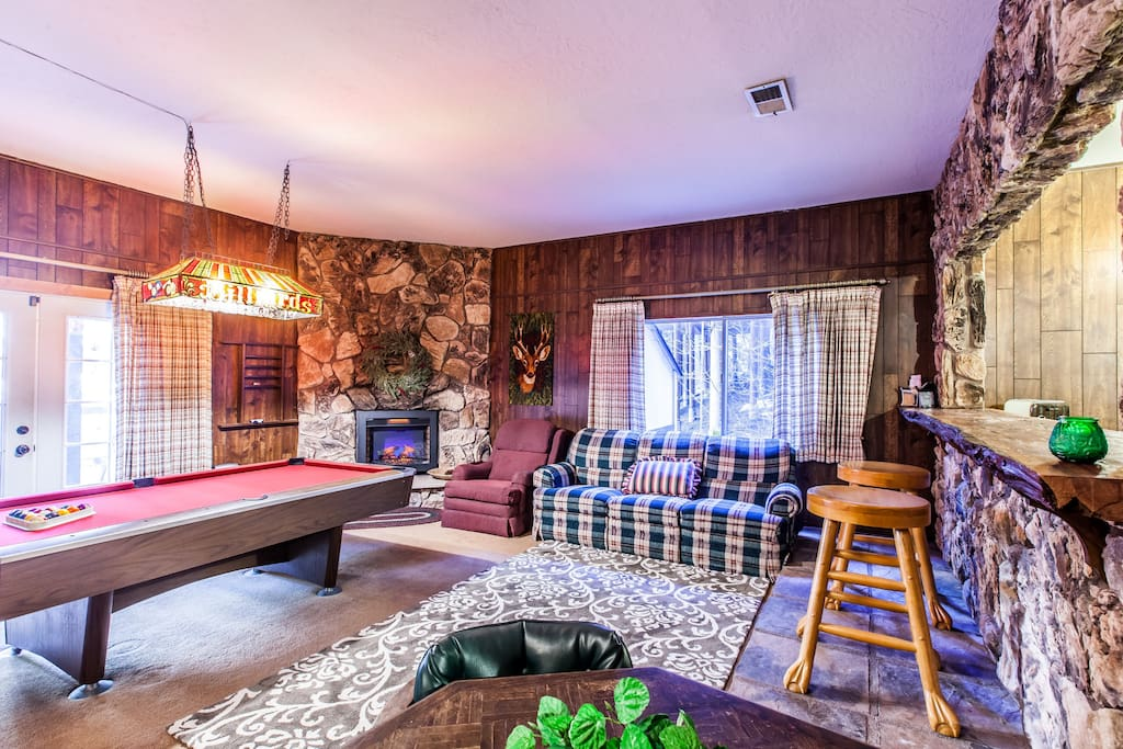 Living room with pool table and fireplace surrounded by rock