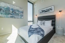 "Master bedroom has floor to ceiling windows, a queen size bed and a 32"" Smart TV."