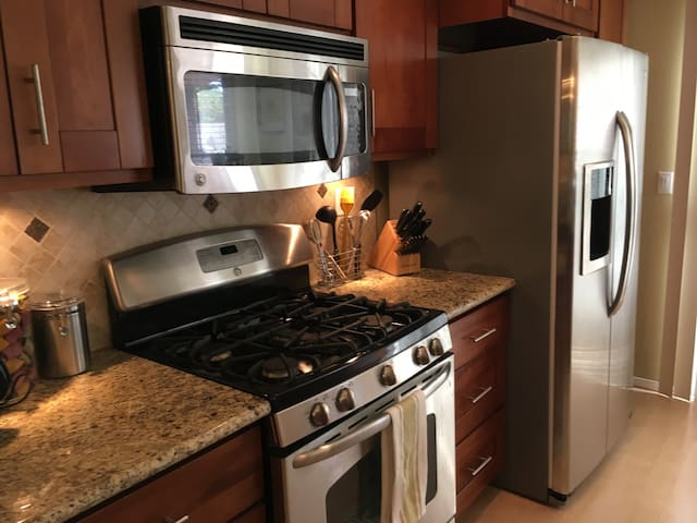 Full kitchen with all stainless steel GE appliances and dishwasher.