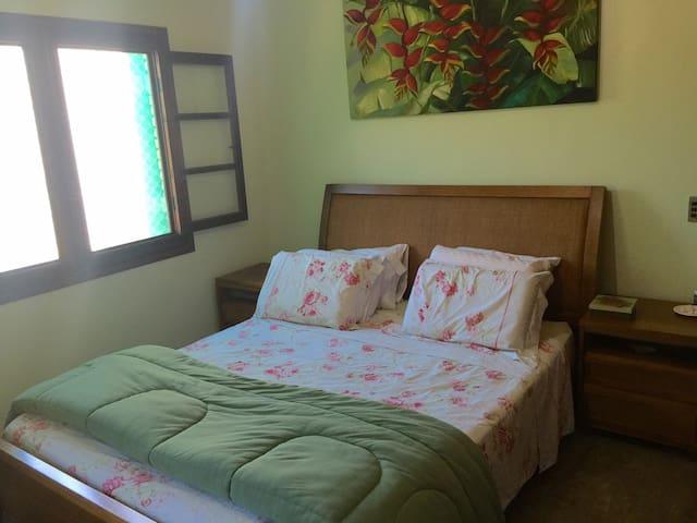 Suíte Casal com ar-condicionado e ventilador de teto e cama Queen.