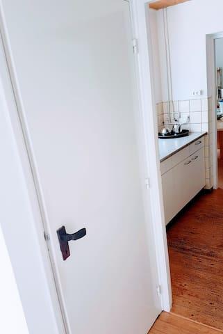 Zicht op keuken en daarnaast een apart toilet. De deurklink is van gesmeed staat, door de kunstenaar gemaakt.