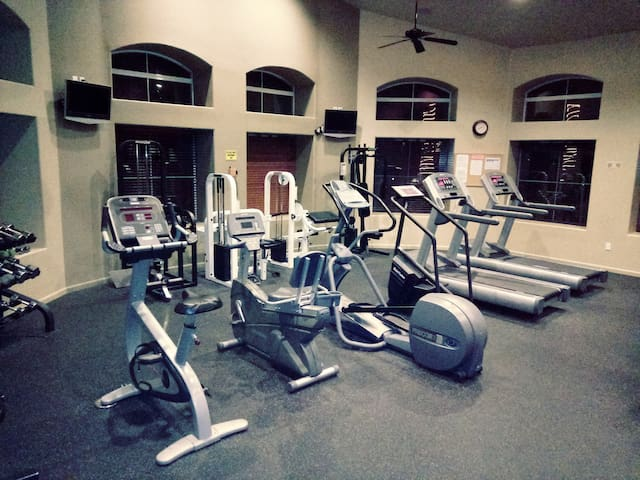 Large exercise gym with new equipment and mounted tv's. Equipment and gym are kept clean