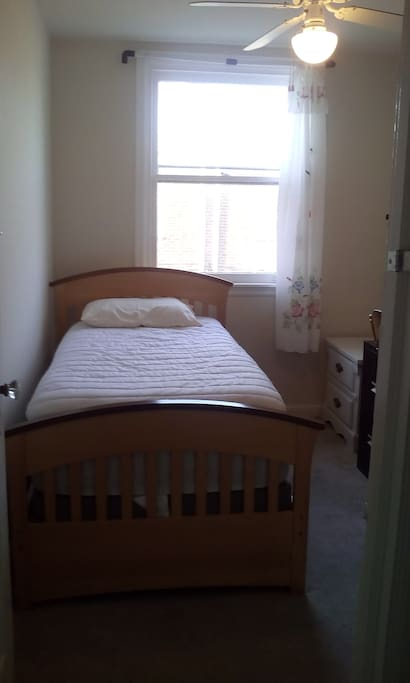 small room with twin sized bed. There are 2 big drawers under the bed.