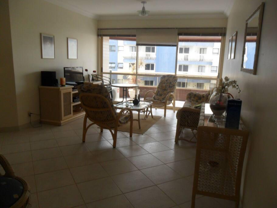 Vista da entrada do apartamento. Ampla sala de estar com mesa de jantar para 4 pessoas, vista para a varanda e uma mesa com 4 cadeiras para a varanda