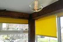 The oak framed sunroom complimented by sunflower yellow blinds and Edison lighting ensures your relaxation.