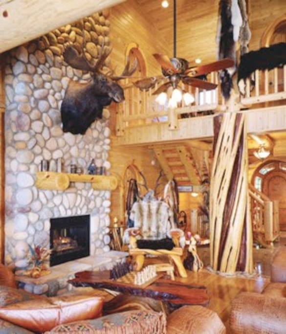 Living room has an amazing view of Lake Michigan. Also features custom made furniture, a huge twisted juniper center log post, gas fireplace, and more.