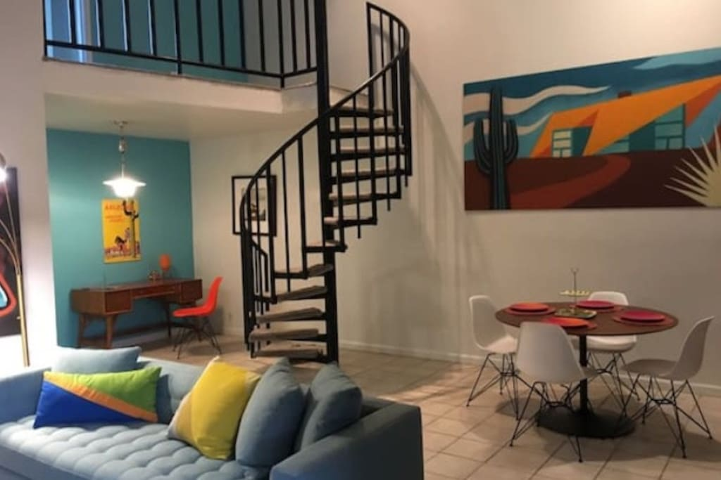 Our loft is an open space. The living room and dining are adjacent as well as a working desk space. The spiral staircase leads to the upstairs bedroom.