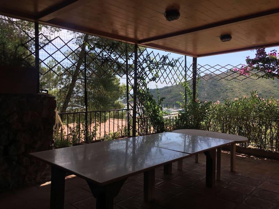 Secondo livello del terrazzo, con grande tavolo per cena e zona cucina esterna.