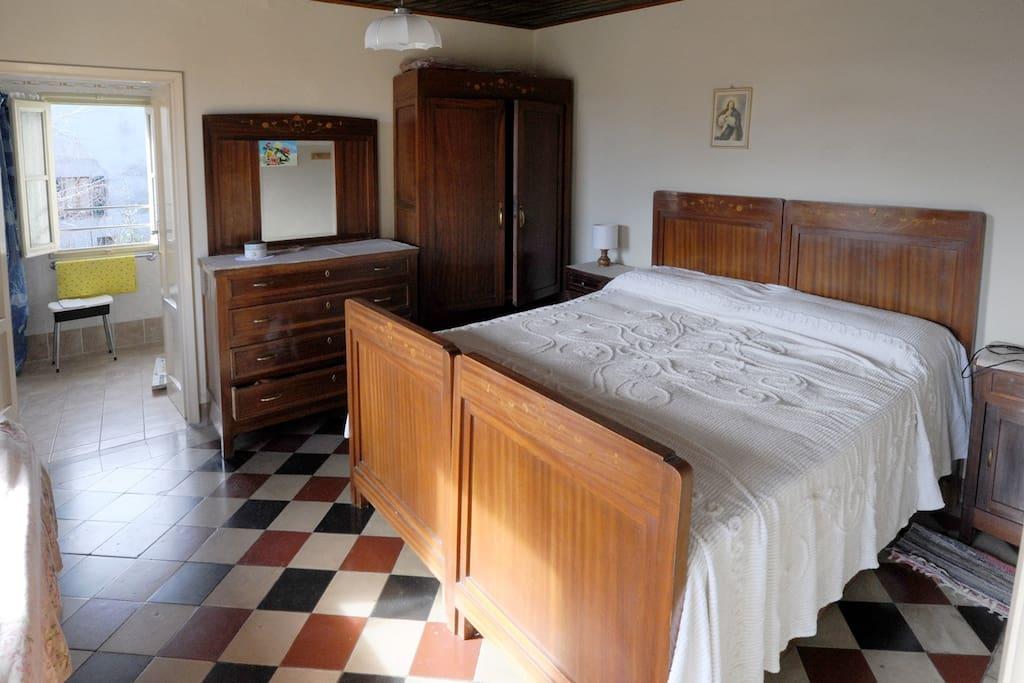 La  camera da letto con il bagno adiacente, con finestra sul giardino.