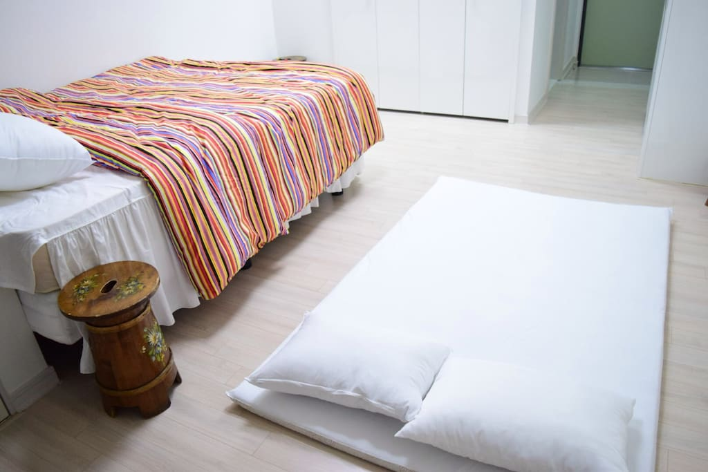 100% cotton bedding and Queen bed for two people. Large Korean-style mattress on the floor for extra person to stay on. Can sleep 3 (Two in queen bed and one on mattress)