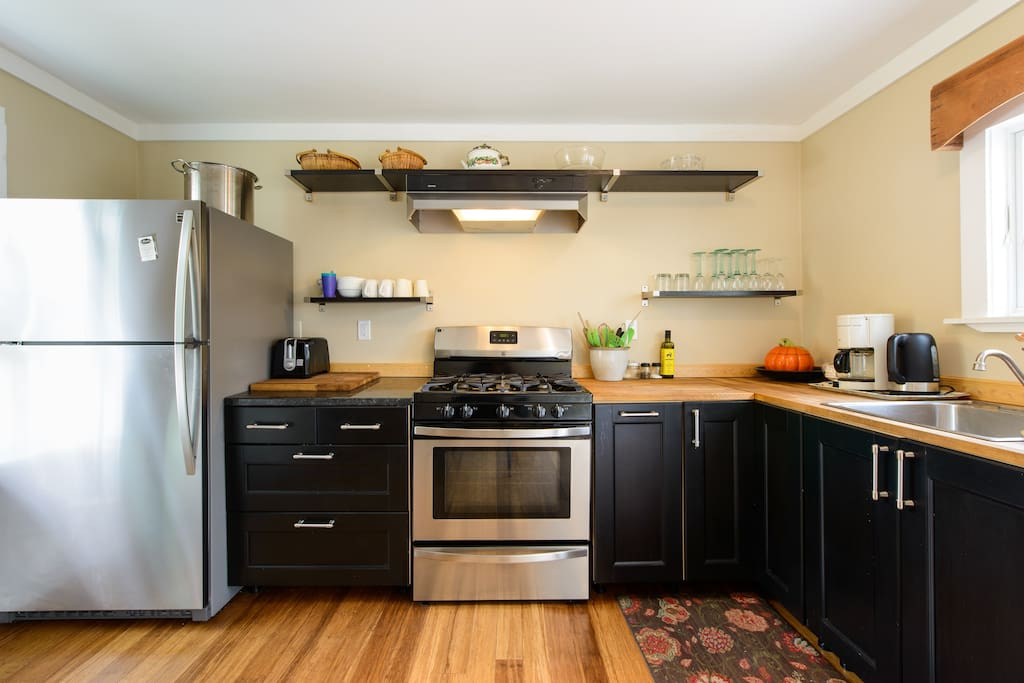 Fully-equipped kitchen with dishwasher, five-burner stove, and full-sized refrigerator