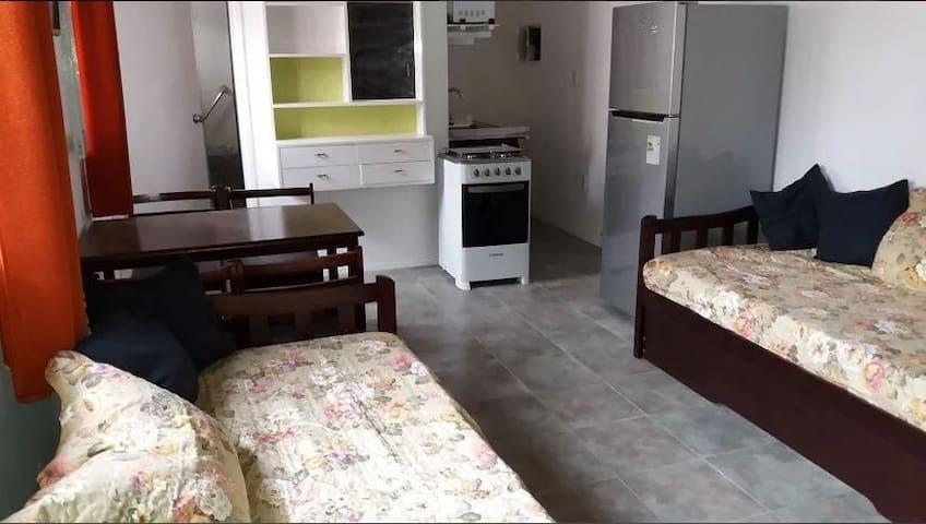 En esta foto se ven las dos camas marineras, la mesa del comedor con sus 4 sillas y al fondo la puerta del baño y la kitchinet.