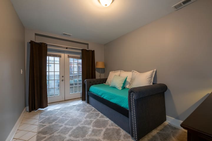 This is the 2nd bedroom - pottery barn day bed, dresser and lighting.  It has a large closet and walks out to an outdoor patio.  This room also has a mini-crib in it with a premium organic mattress. Casper twin mattresses on the day bed. Roku TV.