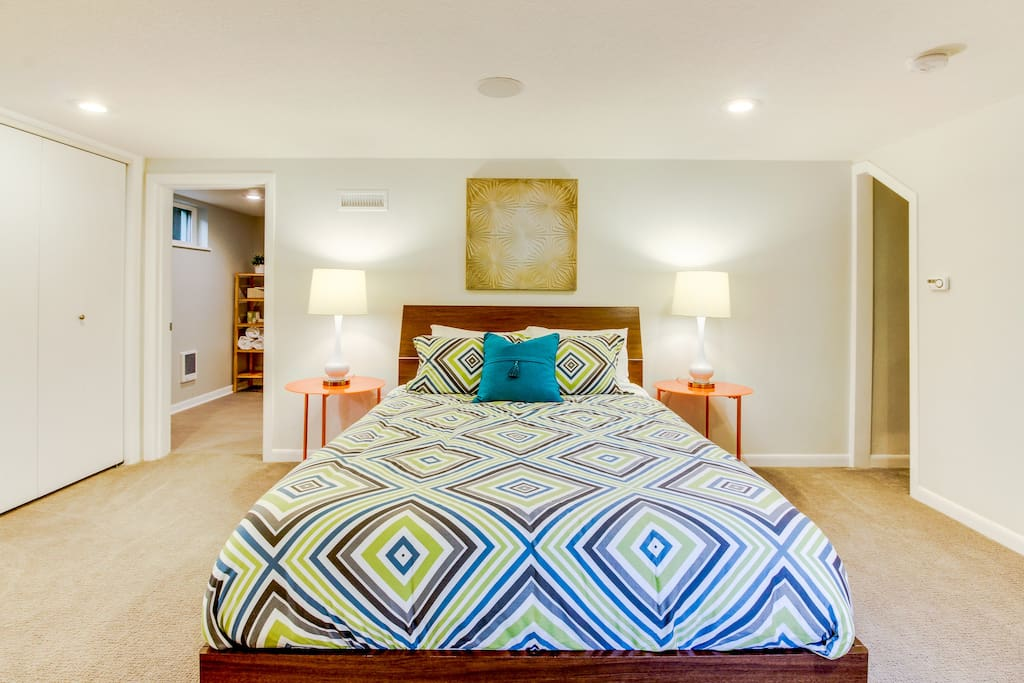 Queen bed in the large and bright bedroom.