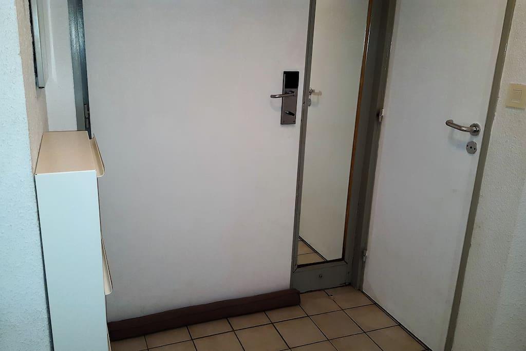 La porte d'entrée et le meuble à chaussures