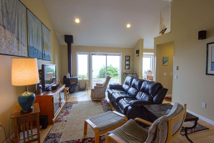 Living room space with seating area for 5, cozy woodstove and local art work.
