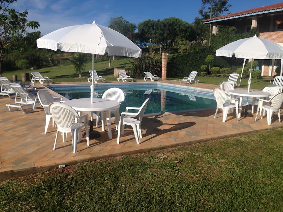 Área da piscina com mesas, cadeiras, guarda-sóis, espreguiçadeiras, tenda e quiosque.
