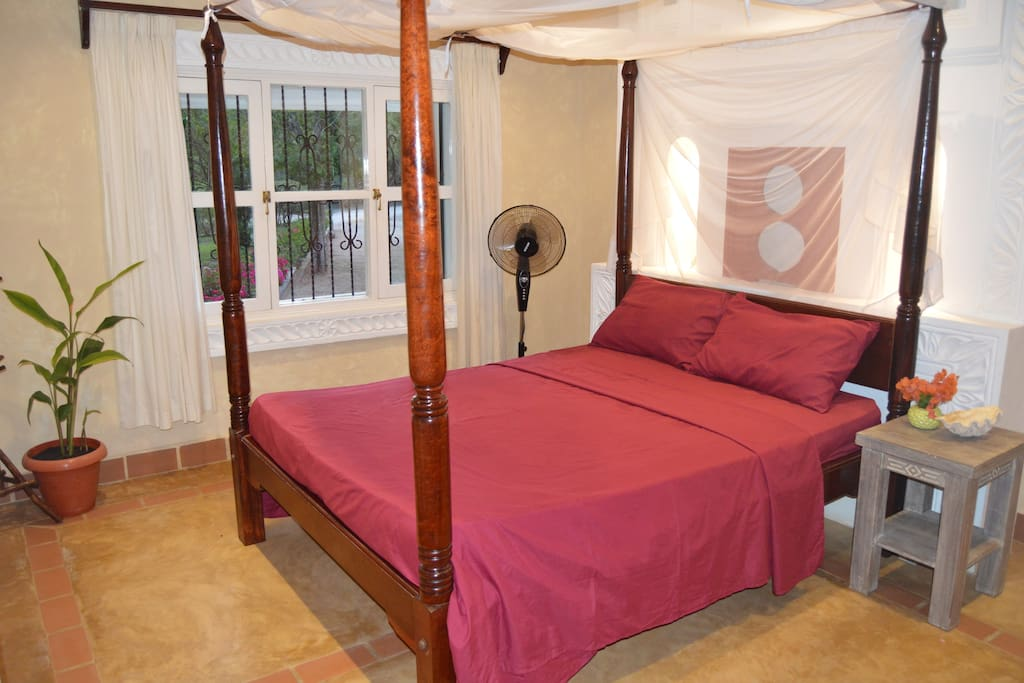 Spacious ensuite bedroom with a fan and mosquito net