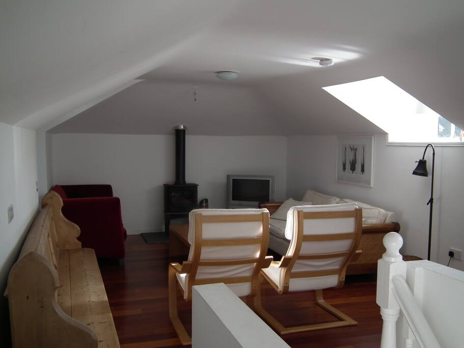 The sitting area with cable TV and wood-burning stove. A settee doubles as an additional single bed.