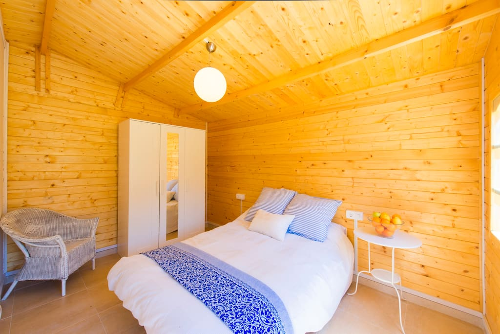The bedroom has a double bed, is decorated with white and blue tones.
