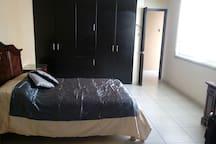 Habitación principal con cama matrimonial, baño completo, tocador y amplio closet.