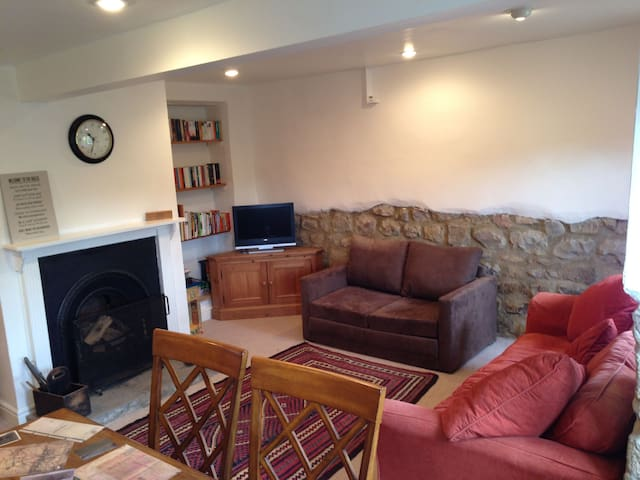 The cottage lounge with squishy sofa, dining table, open fire and plenty of books & games!