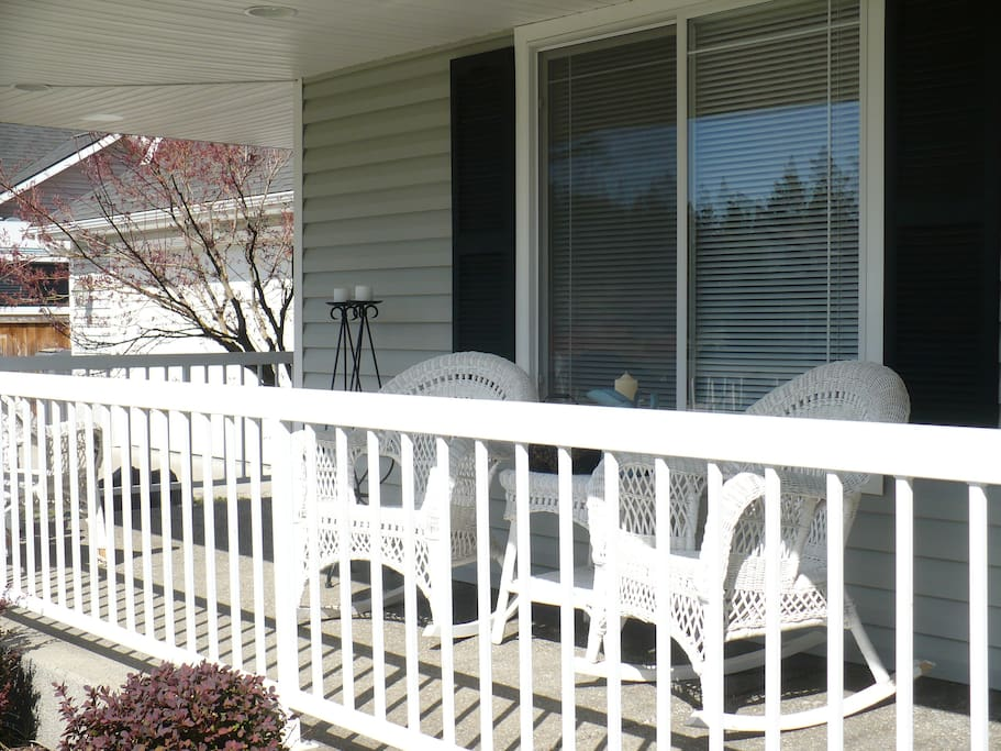 Front porch seating  that wraps around to second entry door and driveway