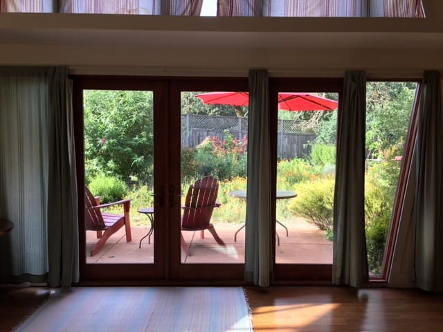 Double doors lead to private porch, views of the garden and towering oak trees.