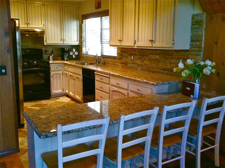 Newly remodeled kitchen with granite countertops and stainless refrigerator.
