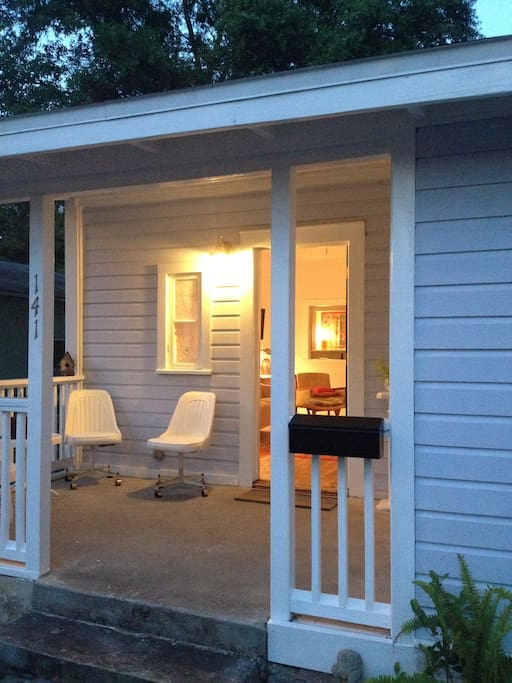 A covered porch with chairs and a side table for enjoying beautiful evenings.