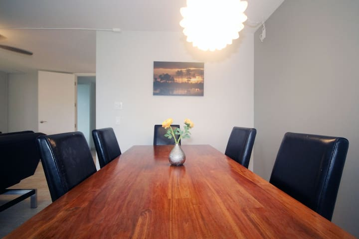 Solid leak dining table with 6 leather chairs.