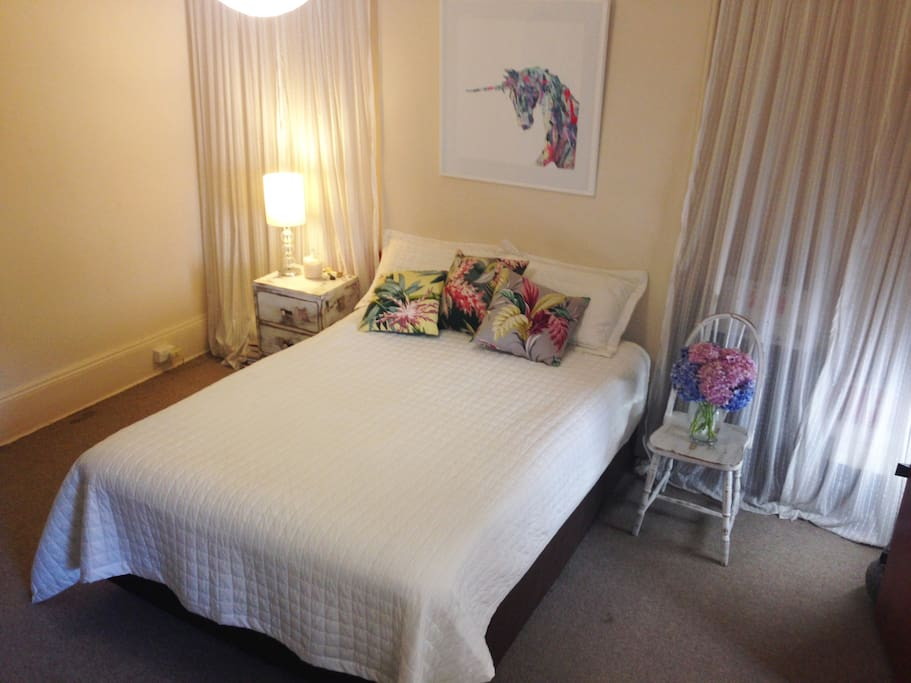 Big spacious bedroom with comfortable queen size bed, clothes rack and heater.