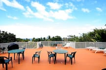 Shared roof-top terrace with BBQ grill and lounge area overlooking Sandy Beach