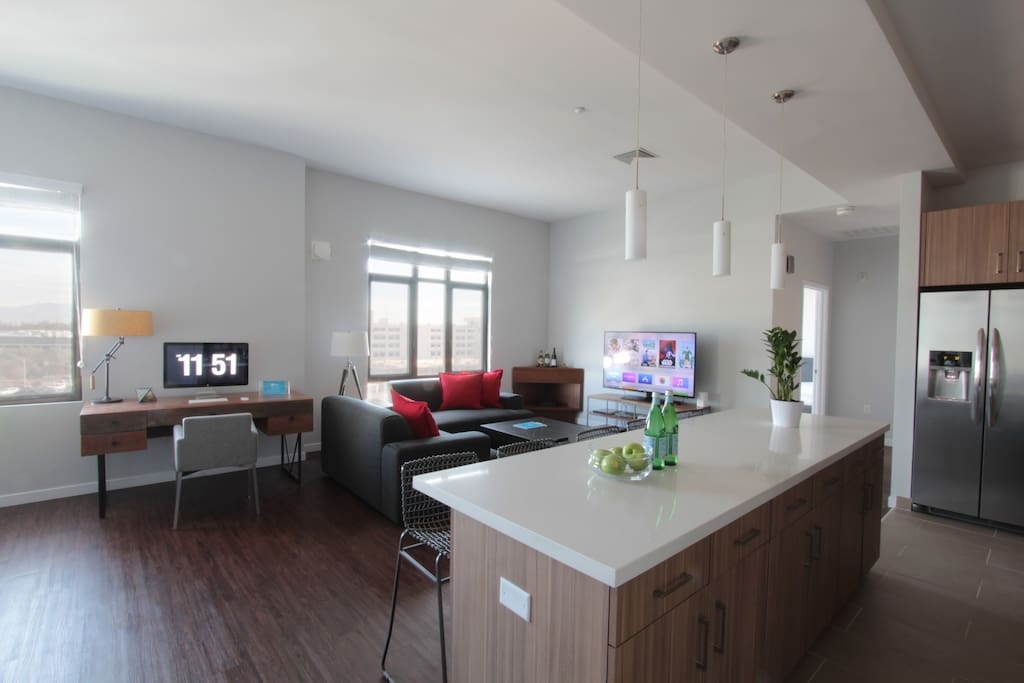 The spacious living room features a workspace, entertainment area and dining area.
