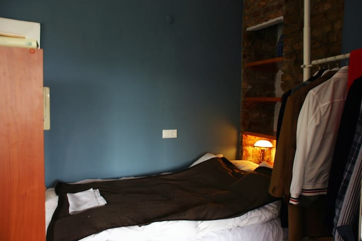 Sleeping area with double bed and exposed bricks