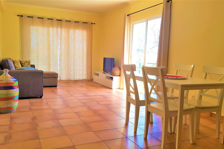 Sala com sofá cama, mesa de trabalho e refeição, varanda e vista mar