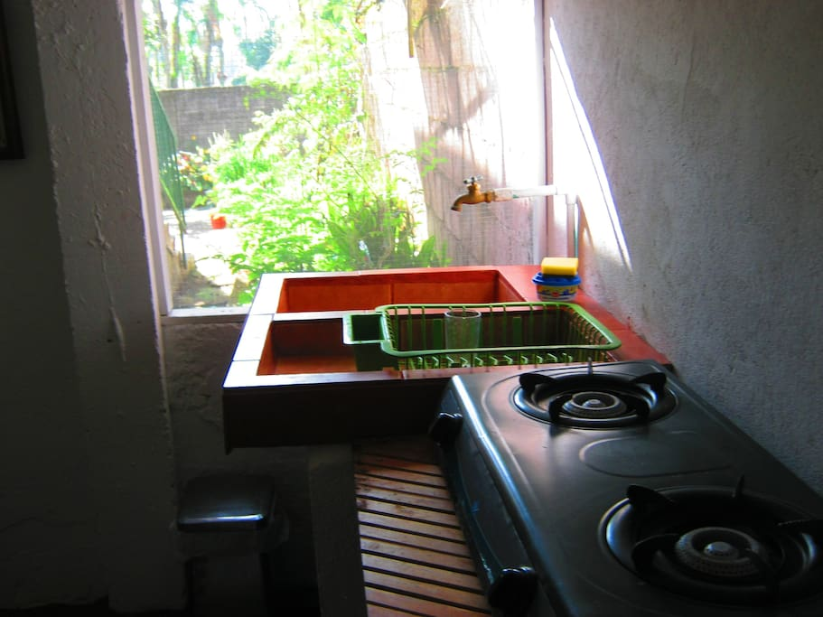 Small view of Kitchen, Gas Stove Top, Basic Double Kitchen Sink and large screened in window facing garden.