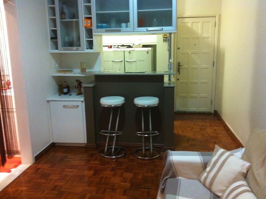 Logo à frente da porta de entrada há bancada com bancos altos, ao fundo a cozinha completa.