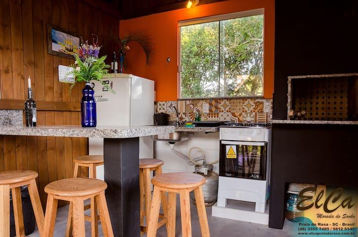 Churrasqueira de uso comum com comodidade de pia, geladeira e fogão.