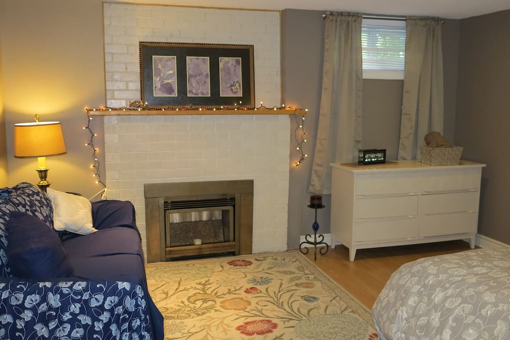 Large bedroom with fireplace, sofa and Queen bed
