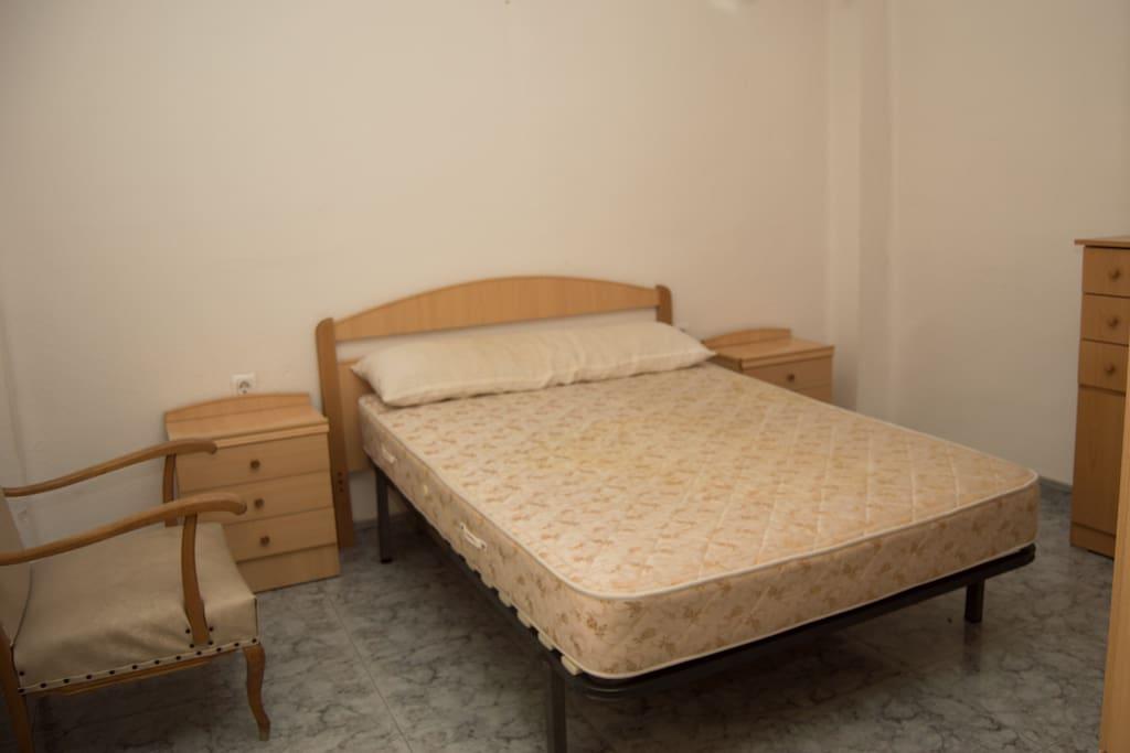 Perspectiva 1 de la habitación con cama de matrimonio. Dos pequeños muebles con cajones a los lados.