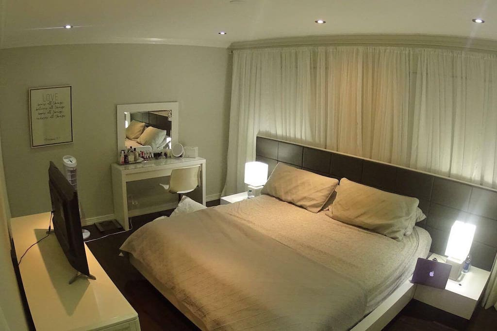 Master bedroom with smart tv and makeup table (walk in closet and private bathroom).