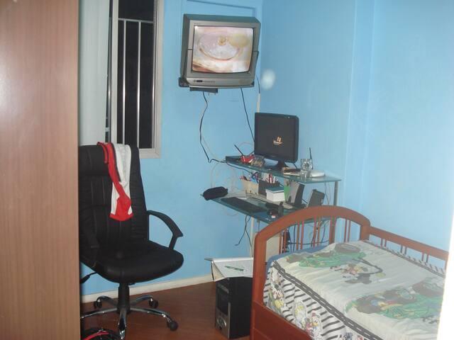 quarto com bicama , televisão e ventilador de teto
