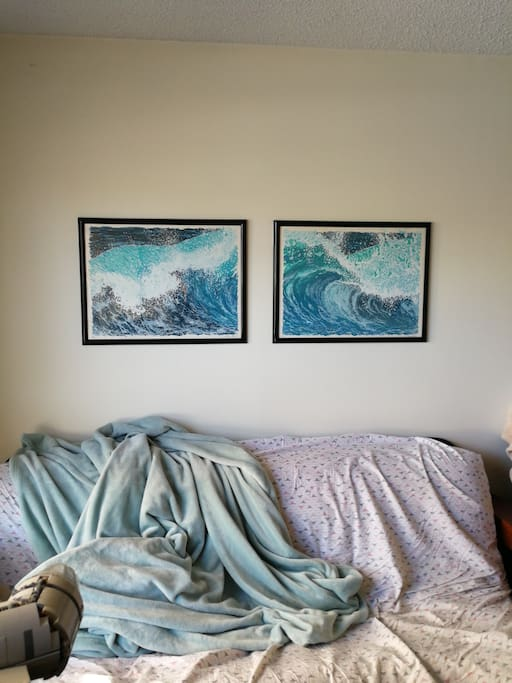 Original art hanging over futon.
