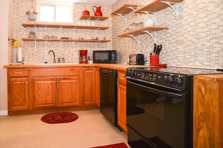 Flat top range, dishwasher, kitchen cabinets, double sinks.