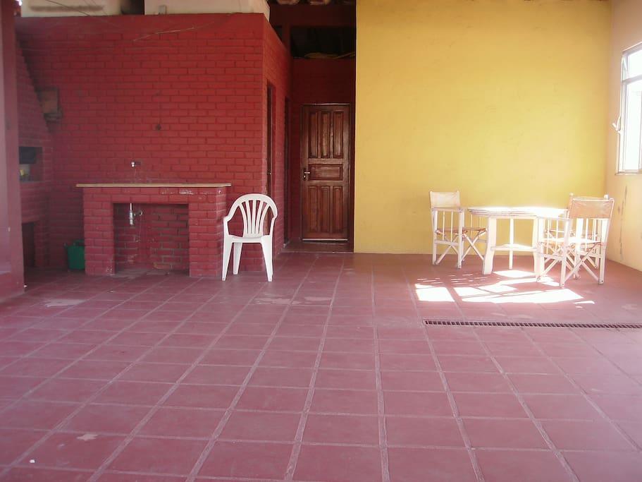 Imagem do terraço, com churrasqueira, banheiro, e 2 quartos.