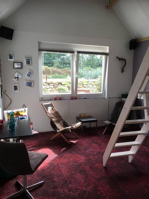 De huiskamer met de trap naar de vide