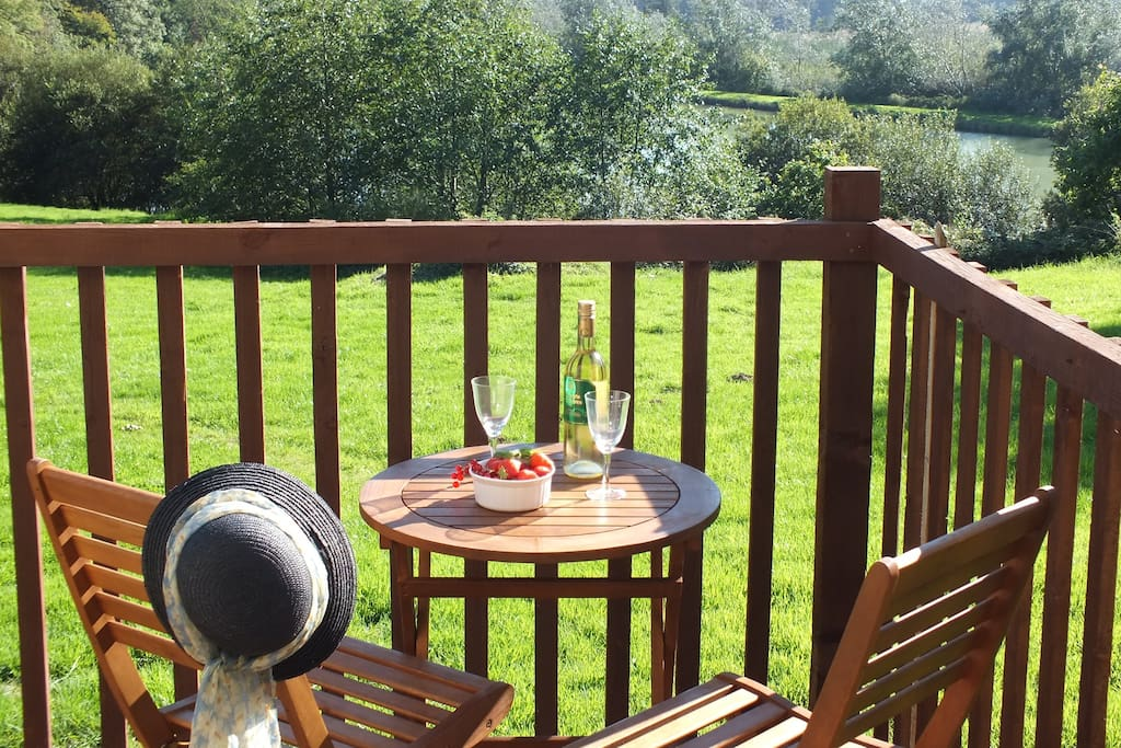 The private, South-facing terrace in Wagtail lodge has stunning views across the lake to the Devon countryside beyond.