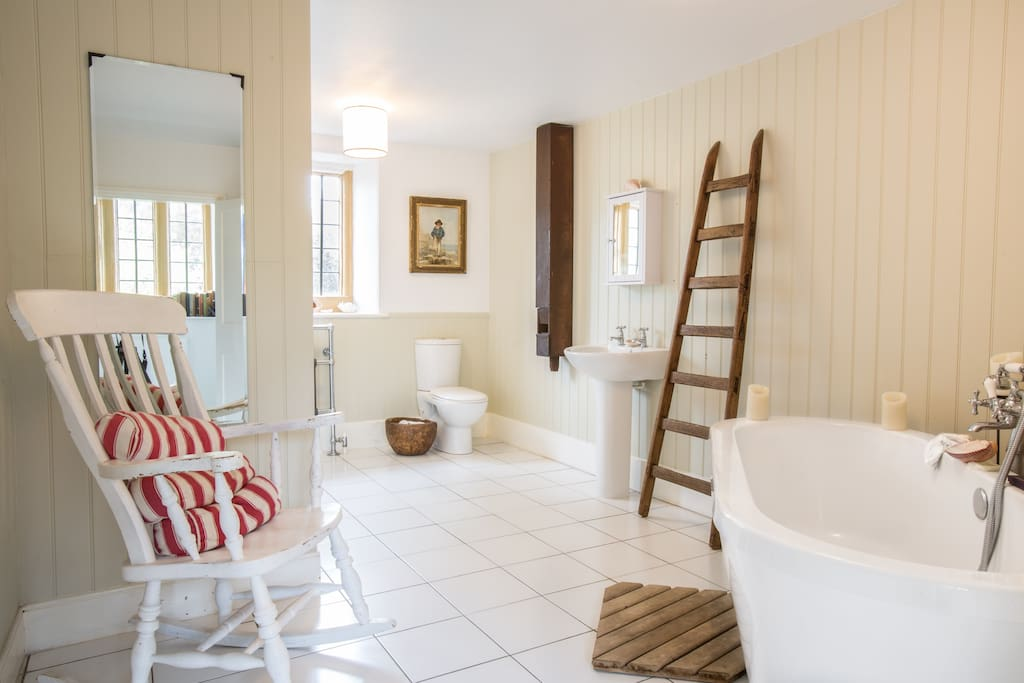 The spacious guest bathroom has a bath to die for and large shower.